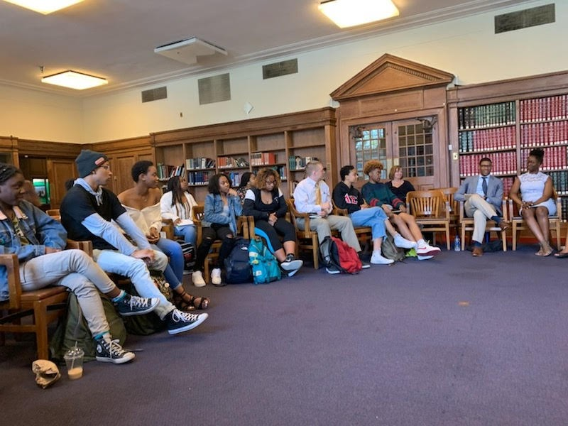 A group of mostly African American students at Howard University are sitting in a semi-circle in a room with bookshelves and purple carpet.