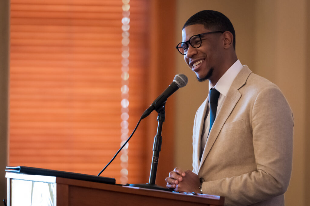 Justin is a Black man standing at a podium smiling into a microphone. He is facing left and wearing a tan suit, white shirt, black tie, and glasses.