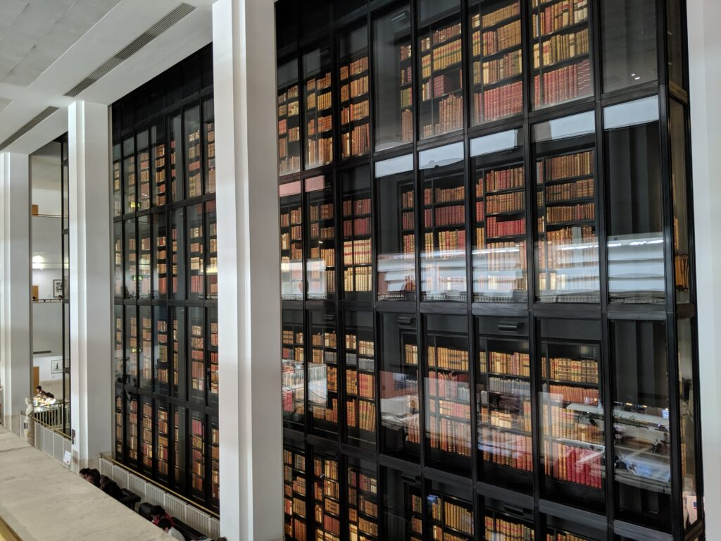 Widescreen photo of atrium in the British Library with large bookshelves behind glass in the background and white pillars in the foreground.